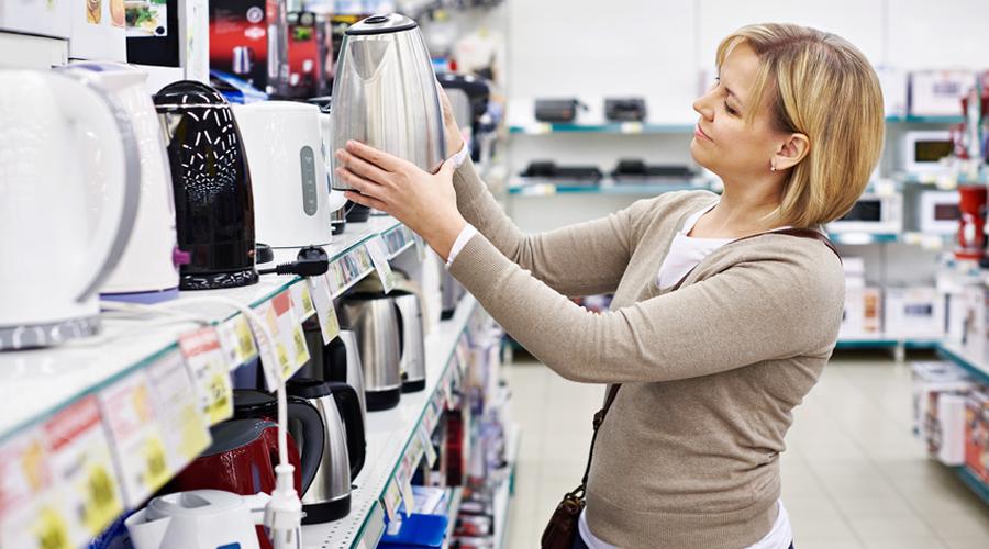 Une femme qui choisit sa bouilloire en magasin