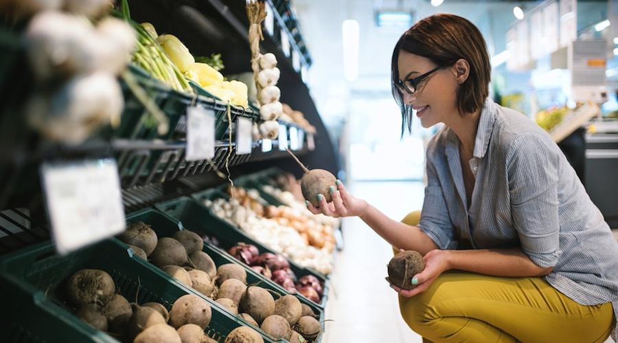femme choisissant légumes supermarché